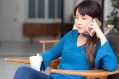 A mulher asi?tica nova do retrato bonito que sorri usando o telefone esperto m?vel que fala para apreciar e beber o caf? com rela imagem de stock