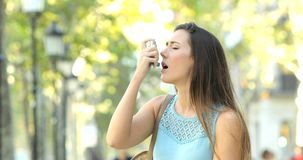Mulher asmática que tem um ataque de asma usando o inalador video estoque