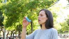 Mulher asmathic adulta que usa o inalador da asma video estoque
