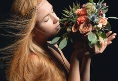 A mulher aspira o ramalhete rústico do vintage do flowe selvagem do cravo das rosas Imagem de Stock Royalty Free