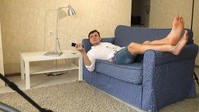 Mulher, aspirador de p30, homem com controlo a distância da tevê, relaxando no sofá A mulher conduz o homem afastado, escolhe vídeos de arquivo