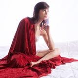 Mulher assentada com cobertura vermelha Imagens de Stock