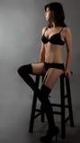 Mulher assentada na roupa interior Imagens de Stock
