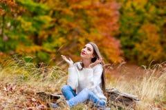 a mulher assentada na terra com braços abre Fotografia de Stock