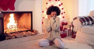 Mulher assentada pela árvore e pelos presentes do White Christmas filme