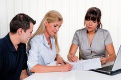 A mulher assina um contrato em um escritório Fotos de Stock Royalty Free