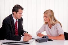 A mulher assina um contrato em um escritório Fotografia de Stock Royalty Free