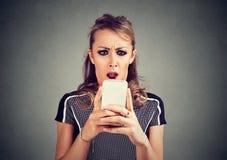 Mulher assustado chocada engraçada que olha o telefone que vê a mensagem das fotos das más notícias com emoção repugnante na cara Fotografia de Stock Royalty Free