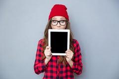 Mulher assustado que cobre sua cara com o tablet pc imagem de stock