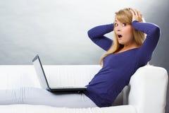Mulher assustado que senta-se no sofá e que olha o portátil, tecnologia moderna Imagens de Stock Royalty Free