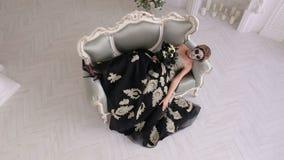 Mulher assustador no vestido e com composição sob a forma das mentiras do crânio em um sofá retro video estoque