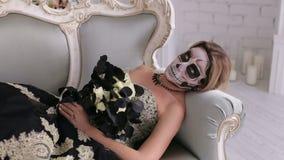 A mulher assustador no vestido e com composição sob a forma de um crânio encontra-se no sofá retro vídeos de arquivo