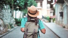 Mulher ativa da trouxa do caminhante da vista traseira no chapéu que anda na rua estreita da cidade europeia acolhedor video estoque