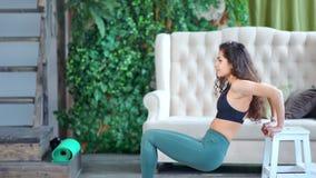 Mulher ativa de sorriso da aptidão que faz o treinamento do exercício em casa que faz o exercício do tríceps usando o banco filme