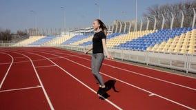 Mulher ativa do ajuste atrativo novo que salta com a corda de salto que dá certo aquecer-se no estádio grande no dia de mola enso vídeos de arquivo