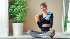 Mulher ativa do esporte que aprecia a ruptura que bebe o suco de laranja fresco da vitamina que senta-se com pé cruzado filme