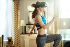 Mulher ativa dos esportes na casa moderna no exercício dos vidros de VR fotografia de stock royalty free