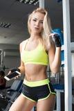 Mulher ativa no sportswear usando o telefone esperto no gym Torne-se melhor Força de vontade Corpo bonito fotografia de stock