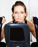 Mulher ativa nova que usa a bicicleta de exercício para o cardio- exercício foto de stock