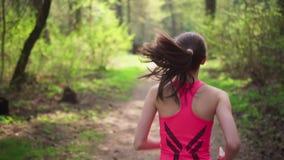 Mulher ativa que corre na floresta ensolarada da mola filme