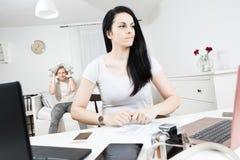 Mulher ativa que trabalha na mesa e no homem furado que esperam no fundo imagens de stock