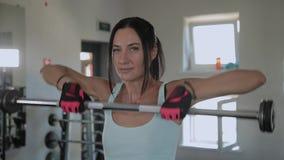 A mulher atlética bonita executa um elevador ao queixo no gym vídeos de arquivo