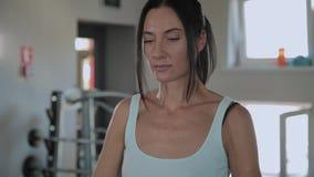 A mulher atlética bonita executa um elevador ao queixo no gym video estoque