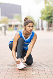 Mulher atlética bonita que amarra suas sapatas antes de exercitar e de t imagem de stock