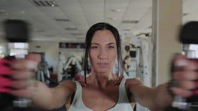 Mulher atlética bonita que faz uma posição do peso filme