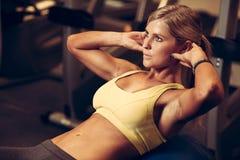 Mulher atlética bonita que trabalha intervalos do ab na aptidão foto de stock royalty free