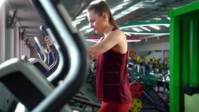 Mulher atlética bonita que usa a escada deslizante ao ter o cardio- exercício no gym vídeos de arquivo