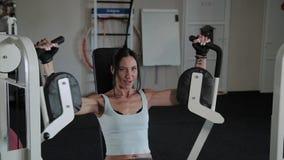 A mulher atlética bonita treina os músculos peitorais no simulador vídeos de arquivo