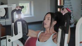 A mulher atlética bonita treina os músculos peitorais no simulador video estoque