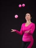 A mulher atlética brutal joga a bola no preto Imagens de Stock Royalty Free