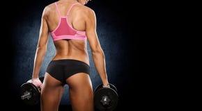 A mulher atlética brutal que bombeia acima muscles com pesos foto de stock royalty free