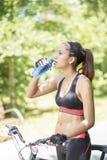 Mulher atlética com a garrafa de água após o exercício com bicicleta, para fora fotos de stock