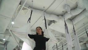 A mulher atlética corrige a rede para a ioga no gym dentro Instrutor que faz a ordem no studion após ter praticado a ioga aérea video estoque