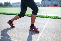 Mulher atlética da vista lateral na pista de atletismo que prepara-se para começar a corrida, atleta amador feche acima dos pés fotos de stock