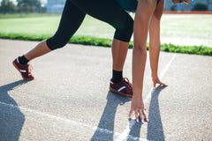 Mulher atlética da vista lateral na pista de atletismo que prepara-se para começar a corrida, atleta amador Pés e braços do close foto de stock