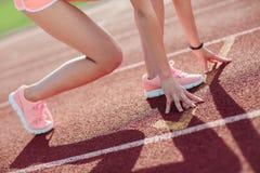 Mulher atlética da vista lateral no short cor-de-rosa e camisetas de alças na pista de atletismo que preparam-se para começar a c imagem de stock
