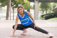 Mulher atlética de sorriso bonita que faz estiramentos antes de treinar imagens de stock