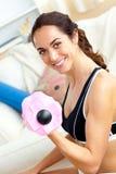 Mulher atlética de sorriso que prende um dumbbell em casa Imagens de Stock