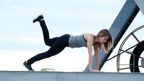 A mulher atlética em uma parte superior cinzenta e em umas caneleiras pretas executa exercícios da força Está no feixe do metal d vídeos de arquivo