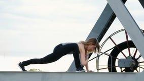 A mulher atlética em uma parte superior cinzenta e em umas caneleiras pretas executa exercícios da força Está no feixe do metal d video estoque