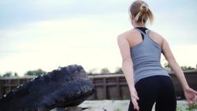 A mulher atlética em uma parte superior cinzenta e em umas caneleiras pretas executa exercícios da força usando uma grande roda p filme