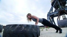 A mulher atlética em uma parte superior cinzenta e em umas caneleiras pretas executa exercícios da força usando uma grande roda d vídeos de arquivo