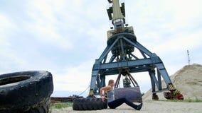 A mulher atlética em uma parte superior cinzenta e em umas caneleiras pretas executa exercícios da força usando uma grande roda d filme