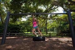 Mulher atlética loura nova que senta-se em um balanço do pneu Imagens de Stock