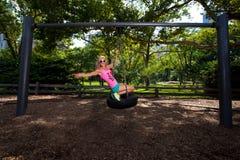 Mulher atlética loura nova que senta-se em um balanço do pneu Foto de Stock