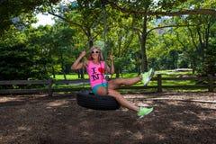 Mulher atlética loura nova que senta-se em um balanço do pneu Fotos de Stock Royalty Free